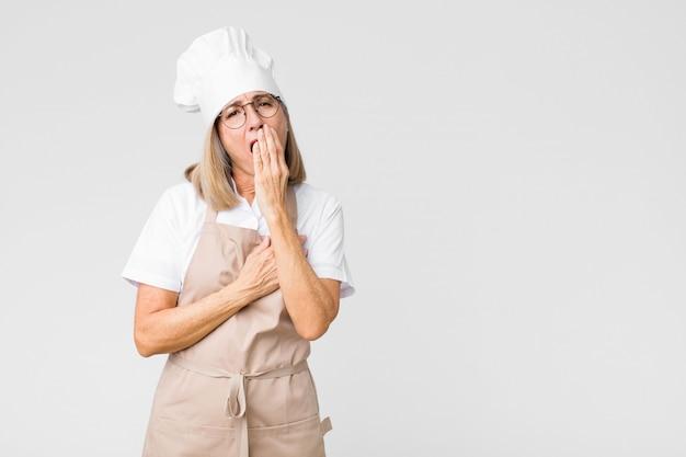 Donna chef che sbadiglia pigramente cercando assonnato stanco e annoiato