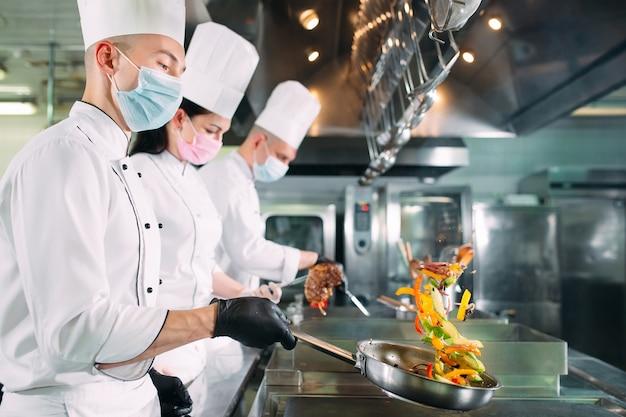 Gli chef con maschere e guanti protettivi preparano il cibo nella cucina di un ristorante o hotel.