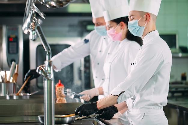 Chef in guanti e maschere protettive preparano il cibo nella cucina di un ristorante o di un hotel.