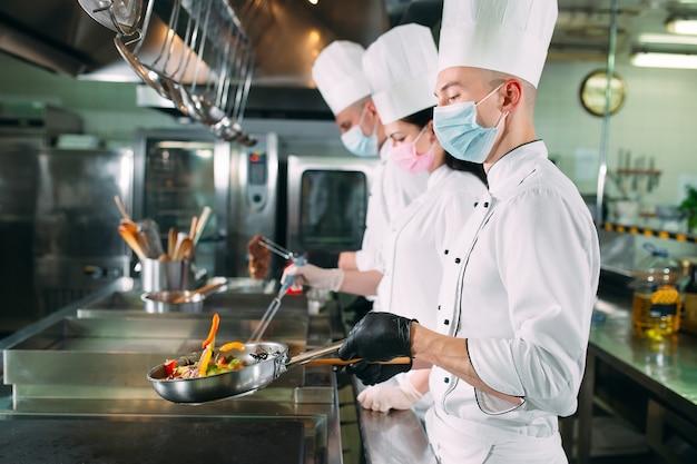Chef in guanti e maschere protettive preparano il cibo in cucina