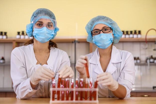 Attrezzature chimiche e due chimici dietro l'esperimento in laboratorio