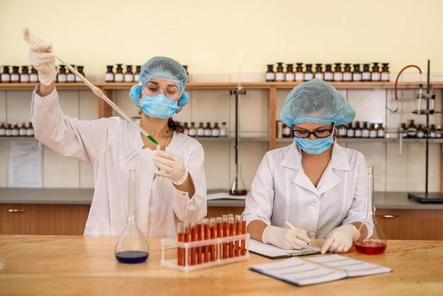 Esperimento chimico in laboratorio. due chimici che esaminano pallone con sostanza liquida