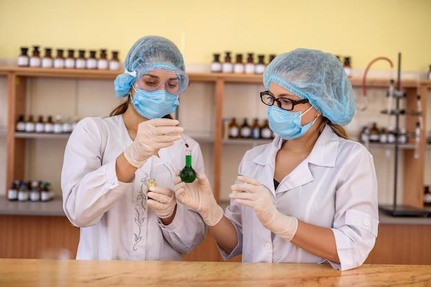 Esperimento chimico.due donne in uniforme protettiva con provette in laboratorio