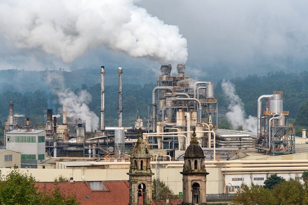 Stabilimento chimico con fumaiolo. emissione di fumo dai tubi di fabbrica. problemi di ecologia e protezione ambientale, inquinamento atmosferico