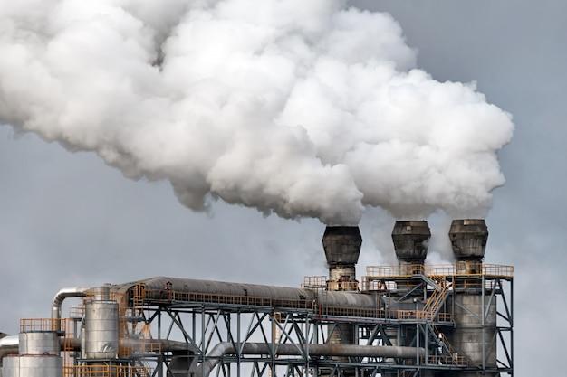 Stabilimento chimico con fumaiolo. emissione di fumo dai tubi di fabbrica.