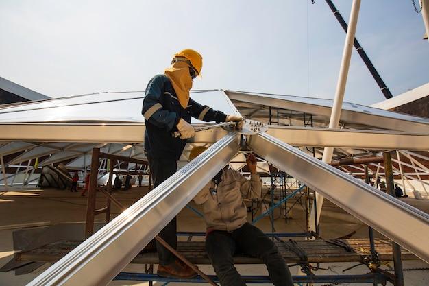 L'industria del lavoratore di sesso maschile di petrolio e gas chimico con serbatoio di stoccaggio del tetto superiore in alluminio a cupola.