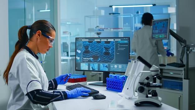 Medico chimico che tiene la provetta con il campione di sangue che inserisce i dati nel pc che lavora in laboratorio. team di scienziati che analizzano l'evoluzione del vaccino utilizzando la diagnosi di ricerca ad alta tecnologia contro il virus covid19.