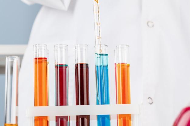 Il chimico passa la tenuta delle provette con i liquidi e fa gli esperimenti