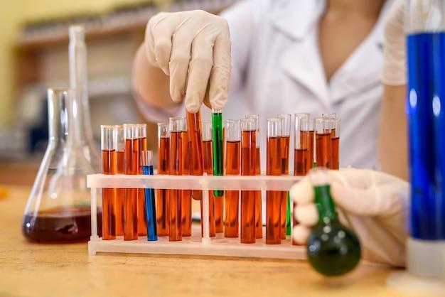 Rack per farmacia con provette di colore rosso e mani umane in guanti protettivi