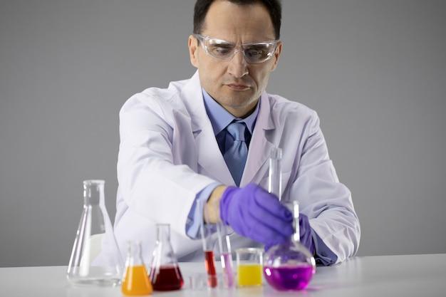 Il ricercatore chimico seleziona soluzioni chimiche colorate piene di boccette