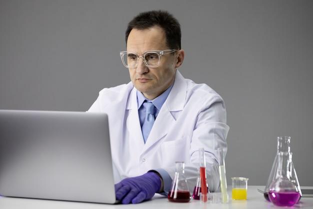 Le boccette di lavoro del ricercatore chimico hanno riempito soluzioni chimiche colorate e laptop