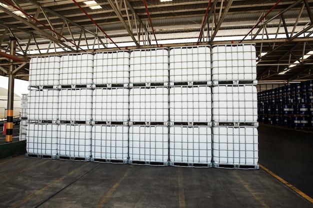 Il serbatoio bianco di chimica su pallet è immagazzinato nella fabbrica del magazzino per essere imballato