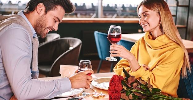 Allegro parlare al ristorante. coppia tenendo il vino rosso in bicchieri nel ristorante. rose rosse e candele sono distesi sul tavolo vicino al vino rosso. la giovane donna in maglione di senape guarda il suo ragazzo