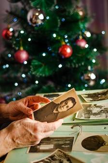 Cherkasy / ucraina - 12 dicembre 2019: mani femminili che tengono una foto di sua madre sullo sfondo dell'albero di natale