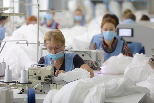 Chernigiv, ucraina - 6 ottobre 2020: cucitura di tute protettive per medici e medici durante la pandemia covid-19 nella fabbrica di cucito tk-style a chernigiv, ucraina