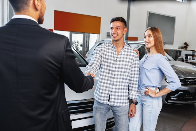 Cherrful giovane coppia presso la concessionaria l'acquisto di una nuova auto