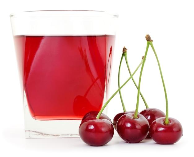 Ciliegie e un bicchiere di succo di ciliegia isolato su bianco