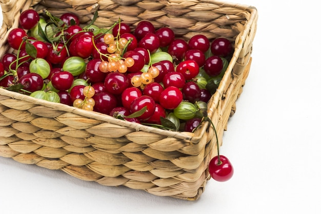Ciliegie, uva spina, ribes in cesto di vimini. sfondo bianco. vista dall'alto
