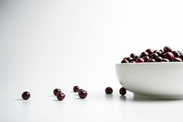 Ciliegie in una tazza bianca su sfondo bianco e accanto alla tazza ciliegie sparse