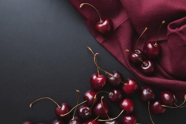 Sfondo di ciliegio. ciliegie su una vista superiore nera. elegante sfondo ricco di ciliegio. sfondo bordeaux con raccolta estiva di bacche di ciliegia. copia spazio, spazio per il testo.