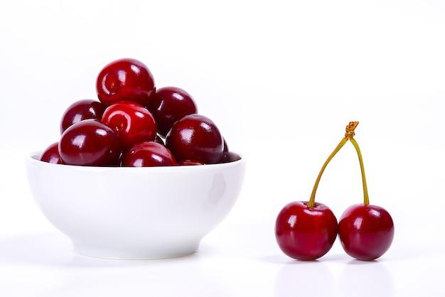 Bacche di ciliegia in una tazza bianca su sfondo bianco. isolato. ciliegie mature. ciliegia rossa deliziosa. posto per pubblicità, scritte, logo, testo, layout, mockup.