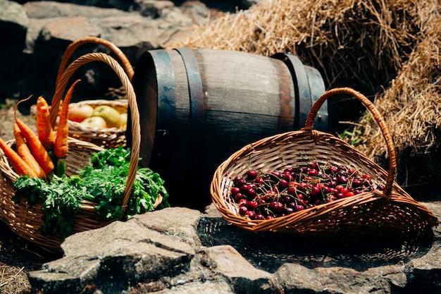 Bacche di ciliegio in un cestino di vimini, un mazzo di carote e una botte di vino sono nel fienile