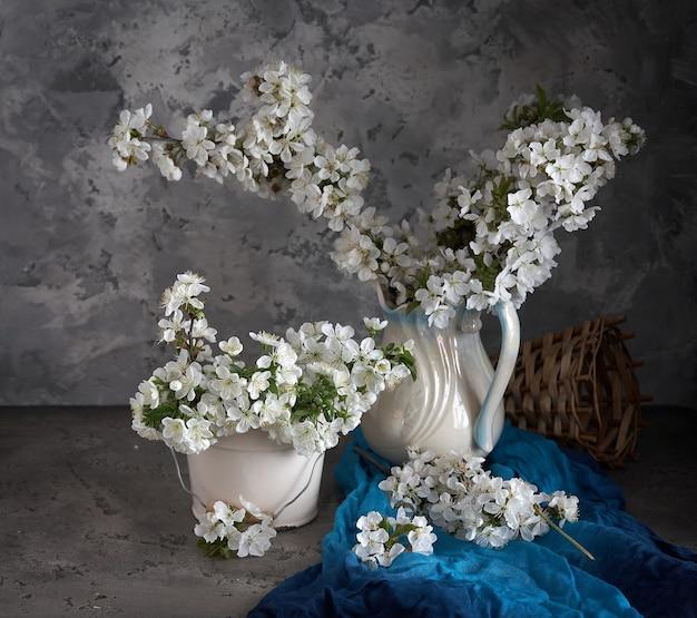 Fiori di ciliegio in vaso bianco su sfondo grigio. primavera ancora in vita.