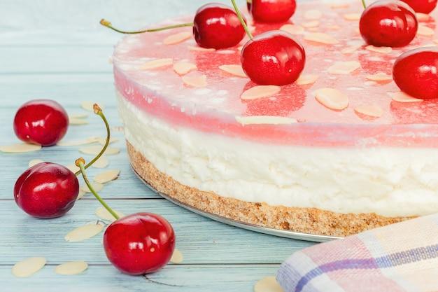 Primo piano della cheesecake alla ciliegia su una superficie di legno chiaro, strati di dessert