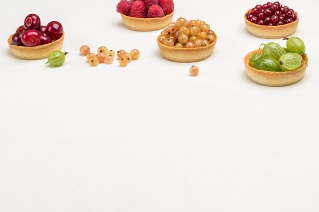 Tartellette di ciliegie, uva spina e ribes. sfondo bianco. vista dall'alto. copia spazio