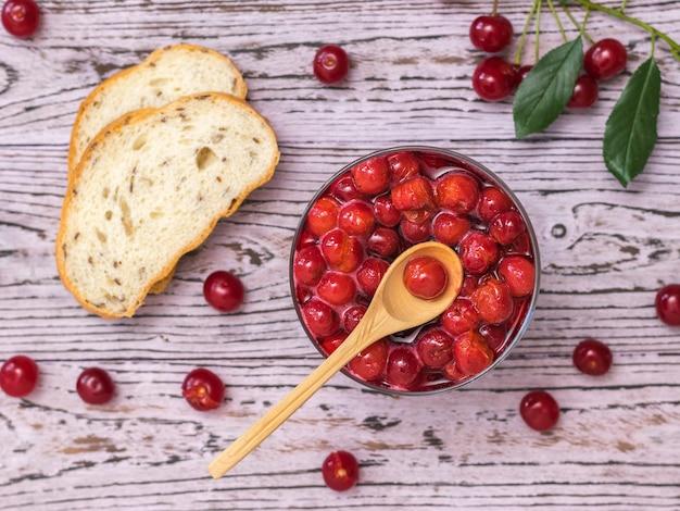 Marmellata di ciliegie e pane con frutti di bosco su un tavolo di legno