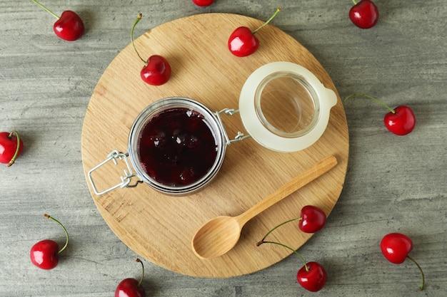 Marmellata di ciliegie e ingredienti sul tavolo grigio strutturato