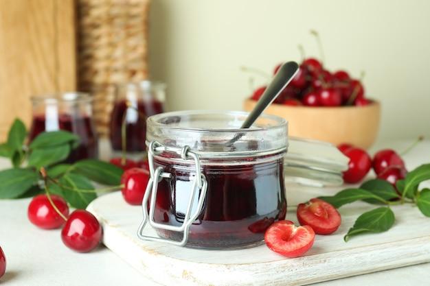 Marmellata di ciliegie e ingredienti sul tavolo bianco strutturato