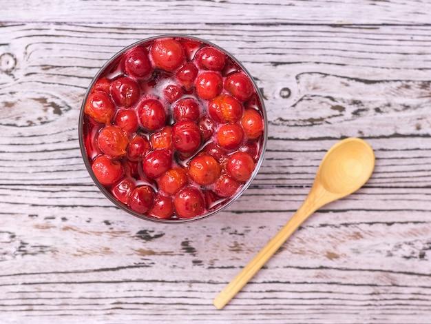 Marmellata di ciliegie e cucchiaio di legno sulla tavola di legno