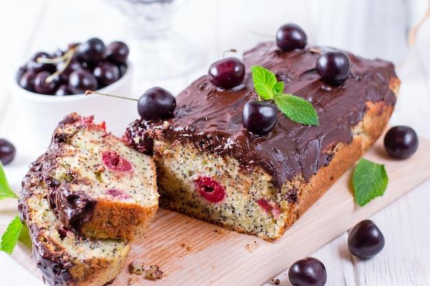 Pan di spagna alla ciliegia e cioccolato su fondo di legno bianco