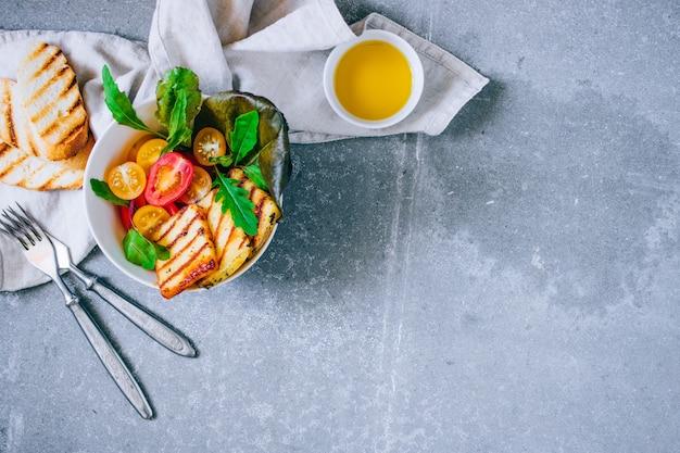 Insalata di pomodori ciliegia con formaggio haloumi grigliato, con bietola e rucola