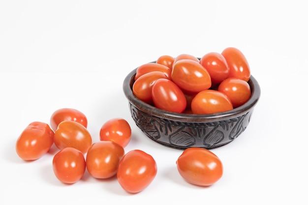 Pomodorini in una ciotola di legno di ebano africano su uno sfondo bianco.