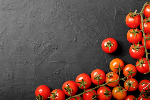 Pomodorini su uno sfondo nero, vista dall'alto.