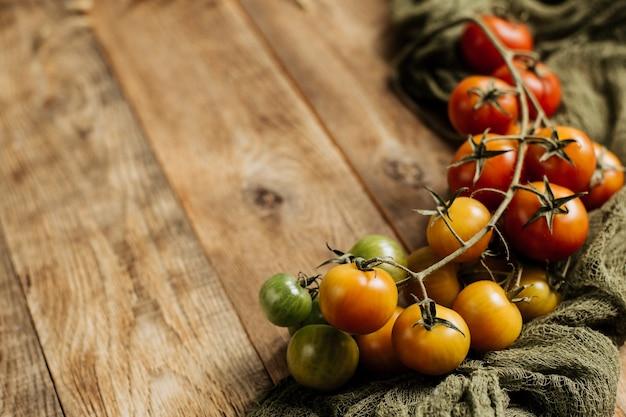 Pomodorini su un ramo su uno sfondo di legno.