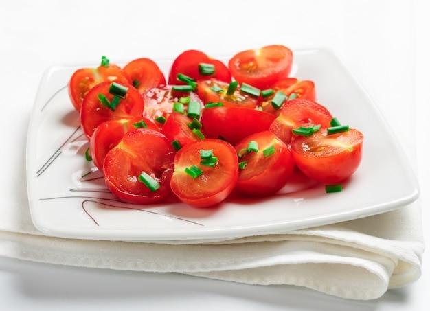 Pomodorini decorati con cipolle verdi. su un piatto quadrato bianco.