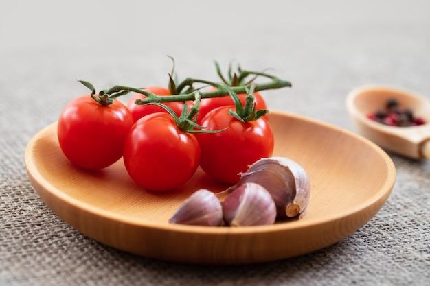 Pomodorini e aglio si chiudono in un piatto di legno su uno sfondo grigio della tela da imballaggio