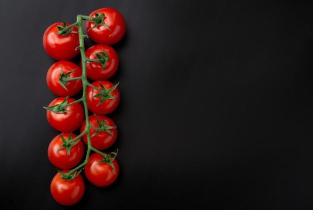 Pomodorini e rosmarino su sfondo nero. ramo di pomodoro fresco. cibo vegetariano.