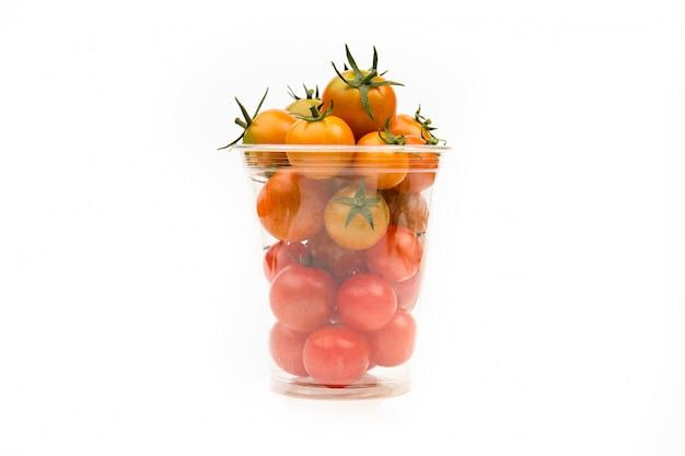 Pomodori ciliegia in contenitore di plastica trasparente su uno spazio bianco, close-up