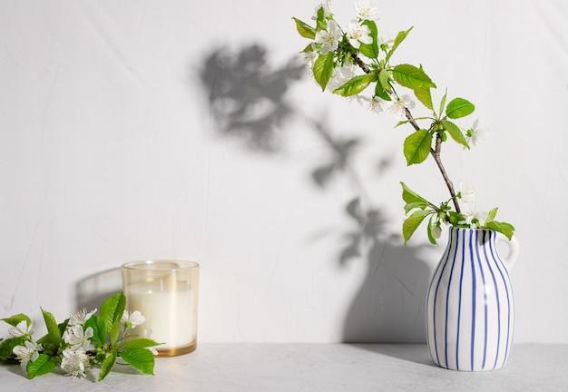 Fiori di ciliegio in vaso a strisce e candela profumata sulla scena di natura morta del tavolo