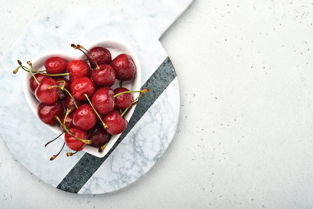 Ciliegia con gocce d'acqua sul piatto a forma di cuore su tavola di pietra bianca. ciliegie mature fresche. ciliegie rosse dolci. vista dall'alto. stile rustico. sfondo di frutta