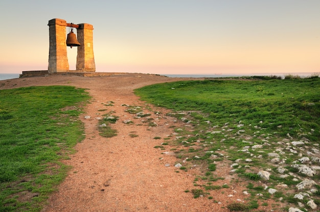 Grande vecchia campana di chersonese vicino al mare su un campo con erba