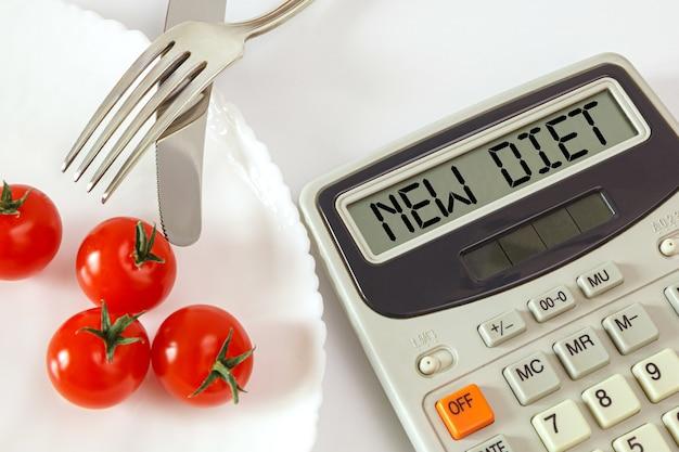 Pomodori chery su un piatto con posate e un calcolatore di calorie