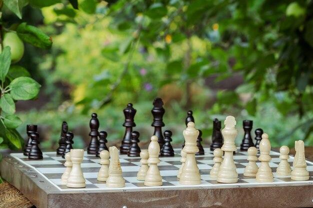 Scacchiera con pezzi degli scacchi su una scrivania con rami di un melo sullo sfondo