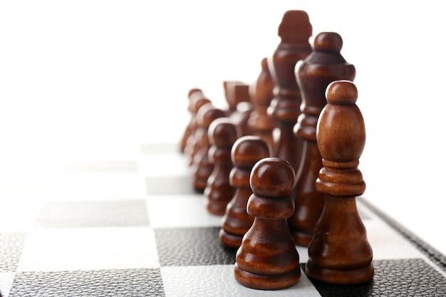 Scacchiera con pezzi degli scacchi su bianco