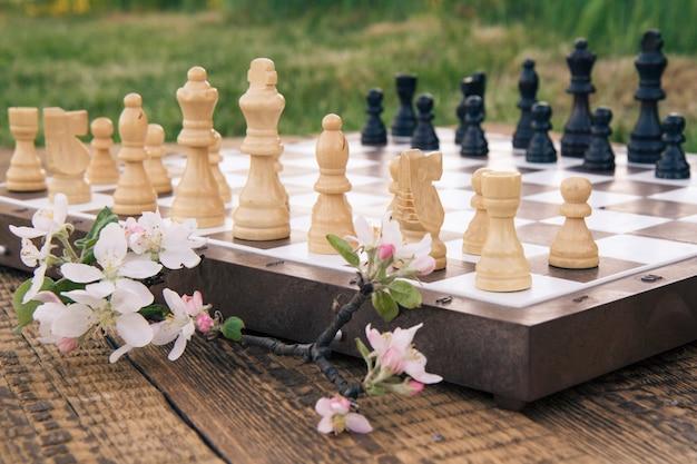 Scacchiera con pezzi degli scacchi sulla scrivania in legno con ramo di melo in fiore ed erba verde sullo sfondo. messa a fuoco selettiva su pezzi bianchi