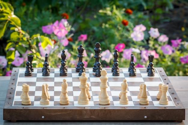 Scacchiera con pezzi degli scacchi sulla scrivania in legno con aiuola sullo sfondo. messa a fuoco selettiva su pezzi bianchi. partita a scacchi all'aperto